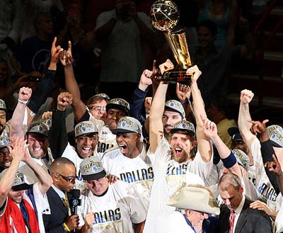 Mark Cuban and the Dallas Mavericks celebrate winning the NBA Championship as Dirk Nowitzki holds up the Trophy