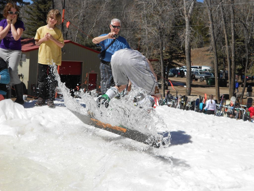 Pond skimming contestant flipping out of pond.